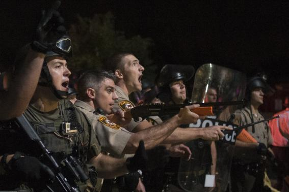 Security forces charge demonstrators after being hit by water bottles during a protest against the shooting of unarmed black teen Michael Brown in Ferguson